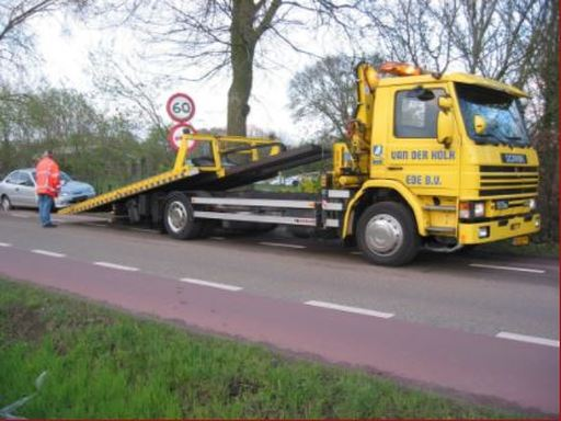 yellow-flat-bed-tow-truck-loading-up-a-car